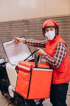Ragazzo delle consegne di cibo alla guida di uno scooter con scatola con cibo e maschera da indossare
