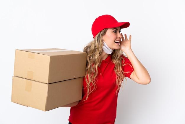 Consegna del cibo donna brasiliana isolata su bianco ascoltando qualcosa mettendo la mano sull'orecchio