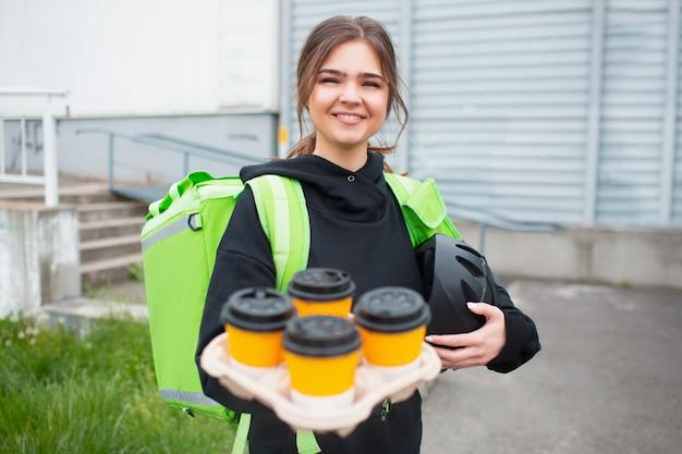Concetto di consegna del cibo. la donna che consegna caffè o tè ha uno zaino da frigo verde.