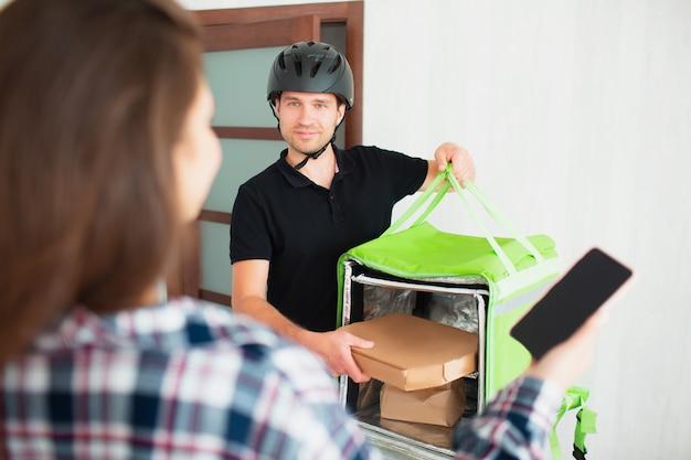 Concetto di consegna del cibo. l'uomo di consegna dell'alimento ha portato l'alimento a casa alla giovane donna.