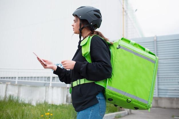 Concetto di consegna del cibo. la donna che consegna i cibi ha uno zaino da frigo verde. vuole consegnare più velocemente e raggiungere i clienti. ci ha portato del cibo