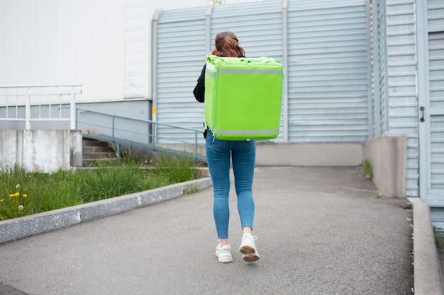 Concetto di consegna del cibo. la donna che consegna i cibi ha uno zaino da frigo verde. vuole consegnare più velocemente e raggiungere i clienti.