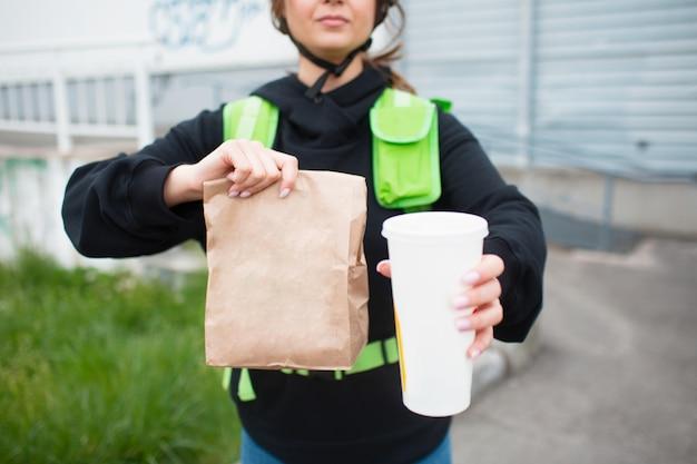 Concetto di consegna del cibo. la donna che consegna i cibi ha uno zaino da frigo verde.