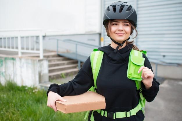 Concetto di consegna del cibo. la donna che consegna le pizze ha uno zaino da frigo verde.