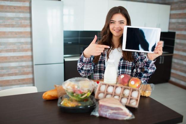 Concetto di consegna del cibo. una giovane donna ordina cibo usando un laptop a casa. sul tavolo ci sono latte, insalate in scatola, carne, cibo, frutta, uova, pane,