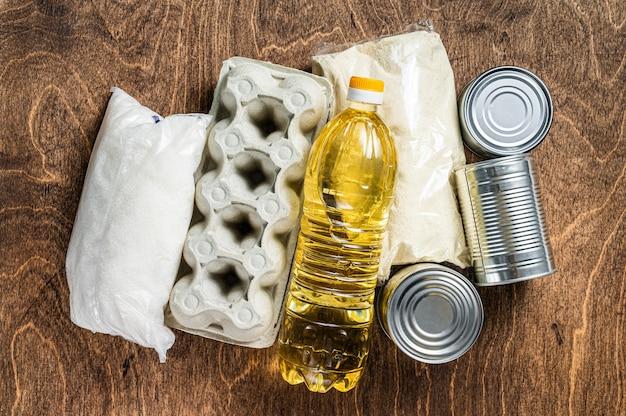Donazione di consegna del cibo, concetto di aiuto in quarantena. olio, conserve, pasta, pane, zucchero, uova. tavolo di legno. vista dall'alto.