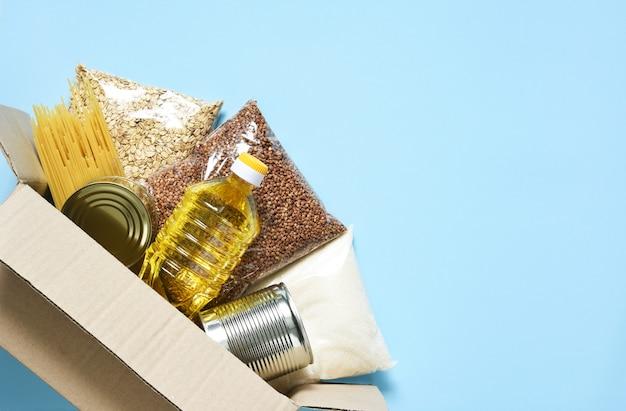 Consegna del cibo. prodotti essenziali: grano saraceno, spaghetti, olio di semi di girasole, cibo in scatola. scatola per alimenti.