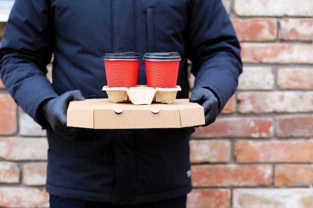 Consegna cibo a domicilio indossando una maschera e guanti.consegna cibo sicuro.