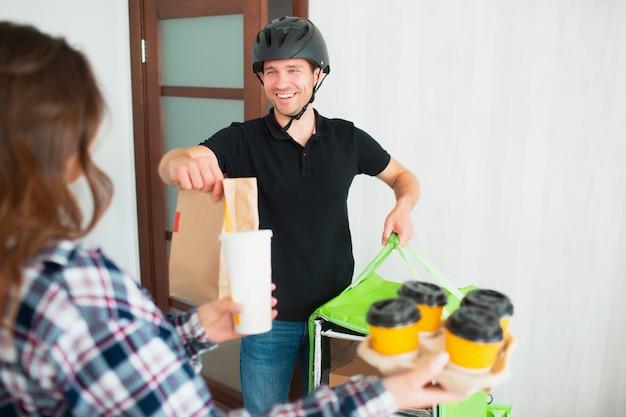 L'uomo di consegna dell'alimento ha portato l'alimento a casa alla giovane donna.