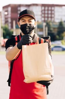 Fattorino di consegna di cibo che tiene sacchetto di carta con cibo in strada all'aperto fattorino a casa in maschera protettiva