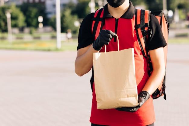 Fattorino di consegna di cibo che tiene sacchetto di carta con cibo in strada all'aperto fattorino a casa in protettivo