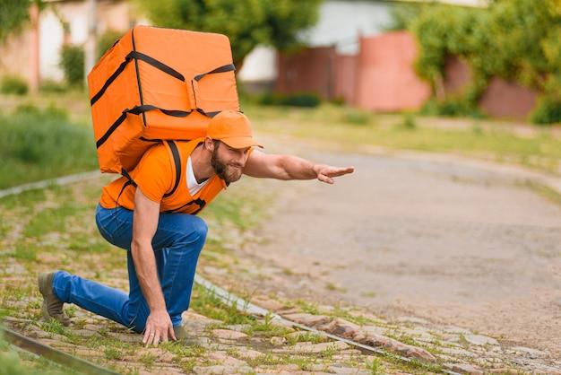 Un uomo che consegna cibo in uniforme arancione con una borsa per la consegna di cibo sulla schiena assume una posa da superuomo