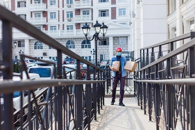 Uomo delle consegne di cibo con borse in una maschera protettiva sul viso