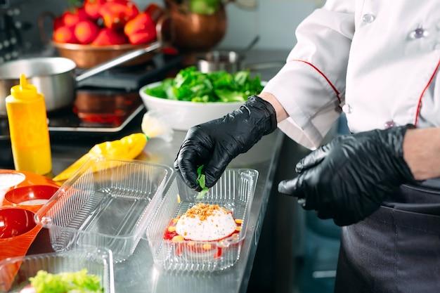 Consegna del cibo nel ristorante. lo chef prepara il cibo nel ristorante e lo confeziona in piatti usa e getta.