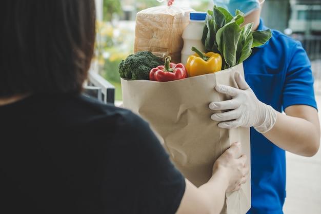 Uomo di servizio di consegna cibo in uniforme blu che indossa una maschera di protezione che tiene il sacchetto di cibo fresco impostato al cliente a casa, consegna espressa, quarantena, epidemia di virus, concetto di consegna di cibo da asporto