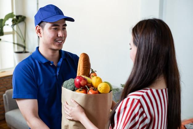 Il personale addetto alla consegna degli alimenti in uniforme blu ha consegnato alimenti freschi al cliente di una giovane donna a casa.