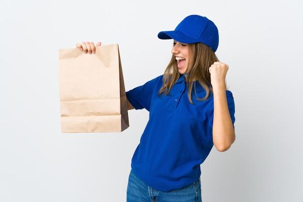Donna che consegna cibo e protezione dal coronavirus con una maschera sul muro bianco isolato che celebra una vittoria