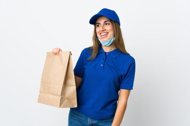 Donna che consegna cibo e protezione dal coronavirus con una maschera sul muro bianco isolato che guarda in alto mentre sorride