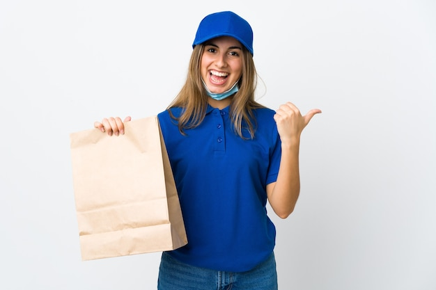 Donna che consegna cibo e protezione dal coronavirus con una maschera sul muro bianco isolato che punta di lato per presentare un prodotto