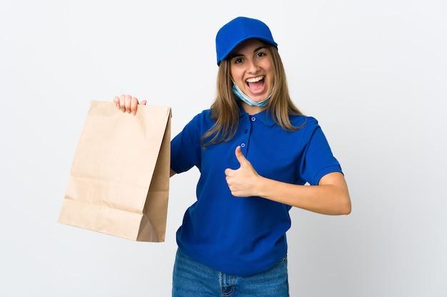 Donna che consegna cibo e protezione dal coronavirus con una maschera sul muro bianco isolato con il pollice in alto perché è successo qualcosa di buono
