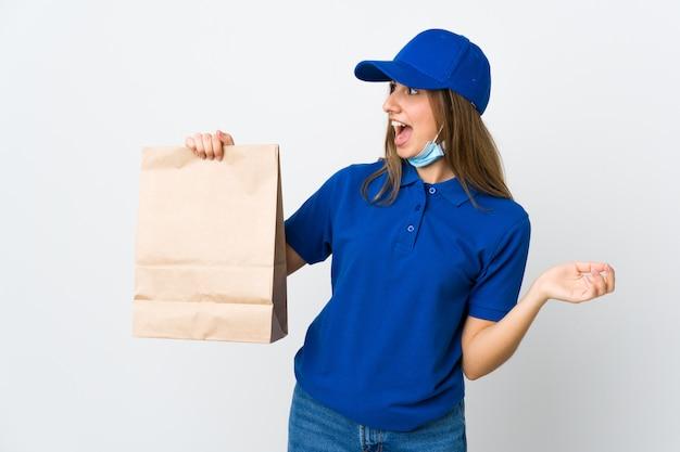 Donna di consegna dell'alimento e proteggere dal coronavirus con una maschera su bianco isolato con espressione facciale di sorpresa