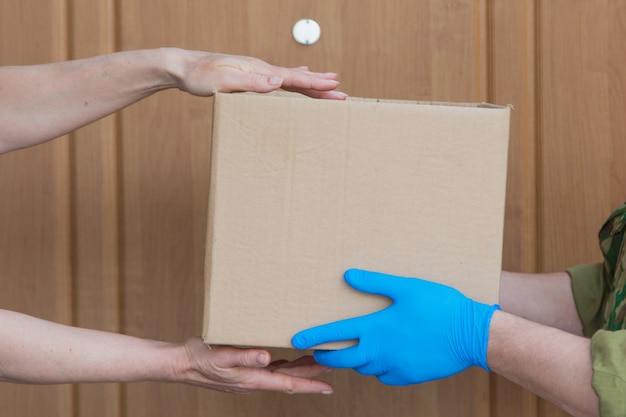 Consegna del cibo a casa tua. assistenza ai pensionati, ai poveri e alla popolazione. un corriere in guanti di gomma passa la scatola. prodotti essenziali alla porta