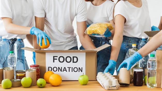 Scatola per la donazione di cibo in preparazione da molti volontari