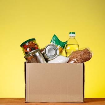 Concetto di donazione di cibo. casella di donazione con il cibo per la donazione su backround giallo. assistenza agli anziani nel contesto della pandemia del coronavirus. immagine quadrata