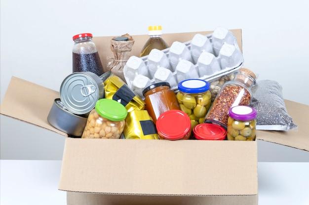 Casella di donazioni di cibo con prodotti alimentari sul tavolo bianco