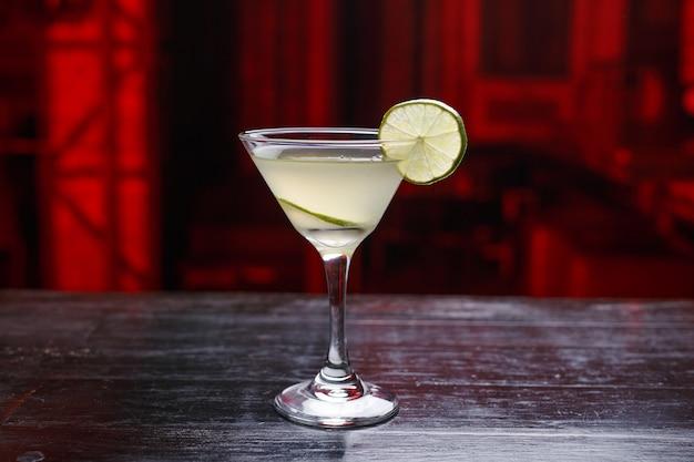 Contenuto di cibi e bevande. cocktail con lime e bordo, in piedi sul bancone del bar, isolato su uno spazio scuro e luminoso.