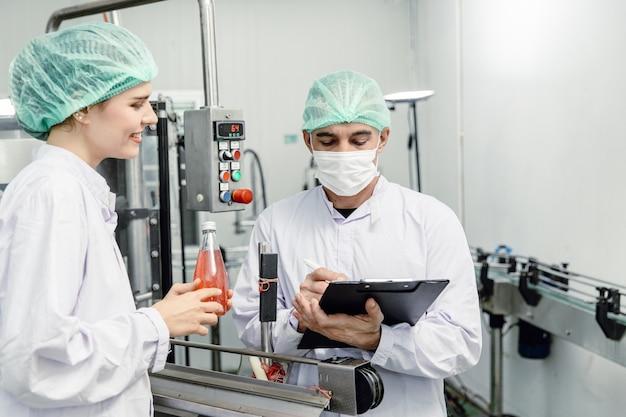 Fabbrica di alimenti e bevande controllo iso del team di controllo della qualità che lavora, controllo dell'igiene e ispezione degli standard di processo nella linea di produzione dell'impianto.