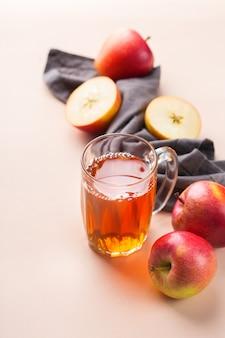 Cibo e bevande, raccolto autunno autunno concetto. succo di mela biologico fresco in una tazza con frutti maturi su sfondo corallo rosa alla moda. copia spazio