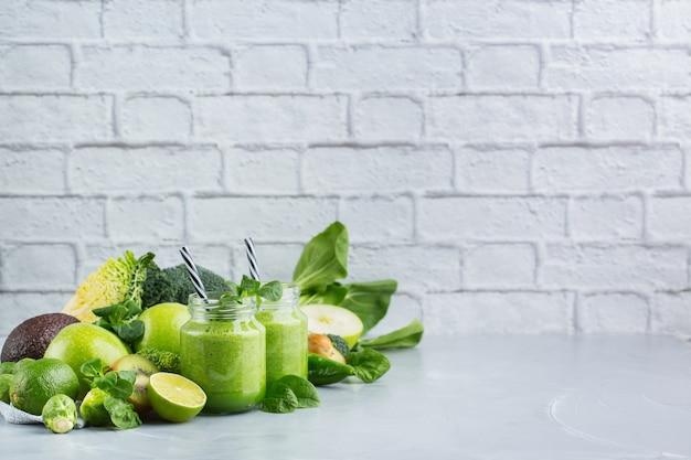 Cibo e bevande, dieta sana e nutrizione, stile di vita, vegano, alcalino, concetto vegetariano. frullato verde con ingredienti biologici, verdure su un moderno tavolo da cucina. copia lo sfondo dello spazio