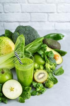 Cibo e bevande, dieta sana e nutrizione, stile di vita, vegano, alcalino, concetto vegetariano. frullato verde con ingredienti biologici, verdure su un tavolo da cucina moderno