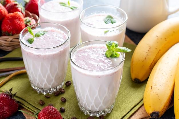 Cibo e bevande, dieta sana e nutrizione, stile di vita, vegano, alcalino, concetto vegetariano. frullato rosa con banana e fragola su fondo di legno vecchio.