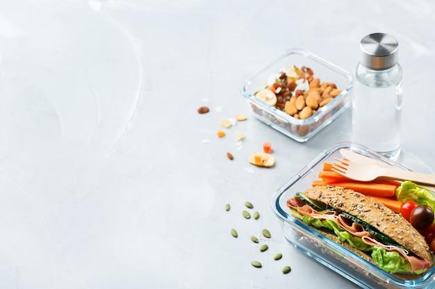 Cibo e bevande, natura morta, dieta e nutrizione, alimentazione sana, concetto da asporto. lunch box con sandwich, frutta, verdura, mix di noci e bottiglia d'acqua. copia lo sfondo dello spazio