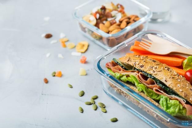 Cibo e bevande, natura morta, dieta e nutrizione, alimentazione sana, concetto da asporto. lunch box con panino, frutta, verdura, mix di noci e bottiglia d'acqua
