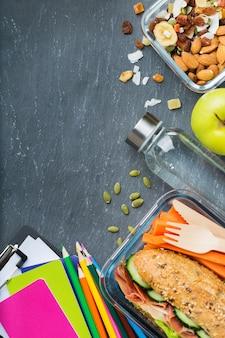 Cibo e bevande, natura morta, dieta e nutrizione, alimentazione sana, concetto da asporto. scatola e cancelleria per il pranzo della scuola. vista dall'alto piatta, copia spazio lavagna sfondo