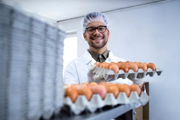 Operaio di fabbrica di cibo in retina per capelli camice bianco e guanti igienici che tengono cassa di uova presso l'impianto di trasformazione alimentare dalla macchina confezionatrice.