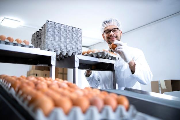 Operaio di fabbrica alimentare in camice bianco e guanti igienici che lavora alla linea di produzione di uova e macchina per l'imballaggio.