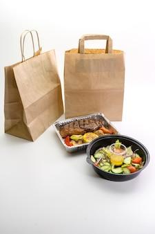 Alimento in un piatto della stagnola e insalata di verdure su una parete bianca. consegna del cibo