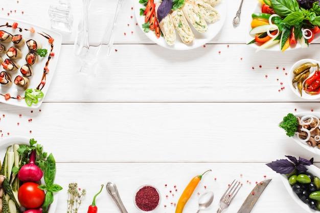 Cornice di cibo sulla tavola di legno bianca