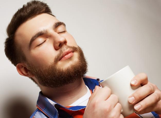 Concetto di cibo, felicità e persone: giovane uomo barbuto con una tazza di caffè su sfondo grigio