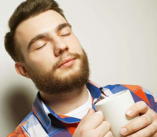 Cibo, felicità e concetto di persone: giovane uomo barbuto con una tazza di caffè su sfondo grigio