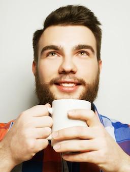 Concetto di cibo, felicità e persone: giovane uomo barbuto con una tazza di caffè contro lo spazio grigio