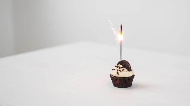 Cibo e concetto di vacanza - bigné di compleanno con lo sparkler sopra fondo bianco con lo spazio della copia.