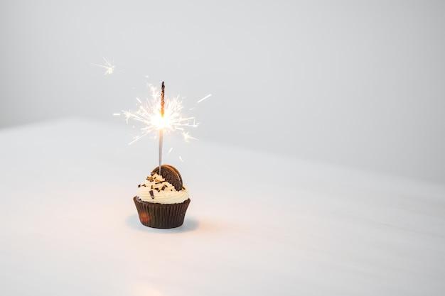 Cibo e concetto di vacanza - bigné di compleanno con lo sparkler sopra fondo bianco con lo spazio della copia. Foto Premium