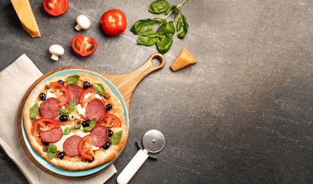 Ingredienti alimentari e spezie per cucinare deliziosi funghi pizza italiana, pomodori, formaggio, cipolla, olio, pepe, sale, basilico, oliva su fondo di cemento nero. copyspace a destra. vista dall'alto. banner
