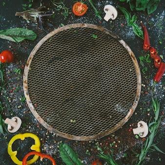 Ingredienti alimentari e spezie per cucinare la pizza. teglia per pizza. funghi, pomodori, formaggio, cipolla, olio, pepe, sale, basilico, grattugia, oliva su fondo rustico. copyspace. vista dall'alto