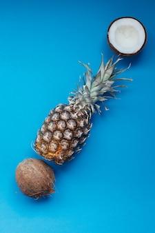 Cibo, minimalismo, colore, natura morta e concetto naturale - ananas fresco e noci di cocco su sfondo blu